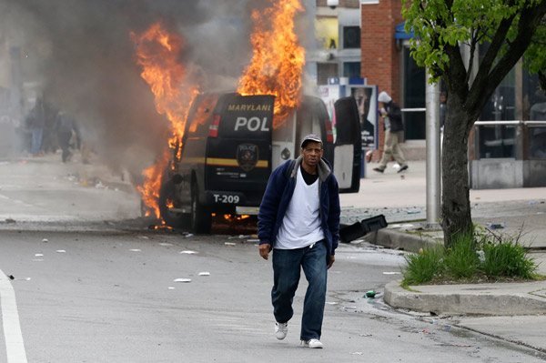 "<div class=""meta image-caption""><div class=""origin-logo origin-image ap""><span>AP</span></div><span class=""caption-text"">A man walks past a burning police vehicle, Monday, April 27, 2015, during unrest following the funeral of Freddie Gray in Baltimore. (AP Photo/Patrick Semansky)</span></div>"