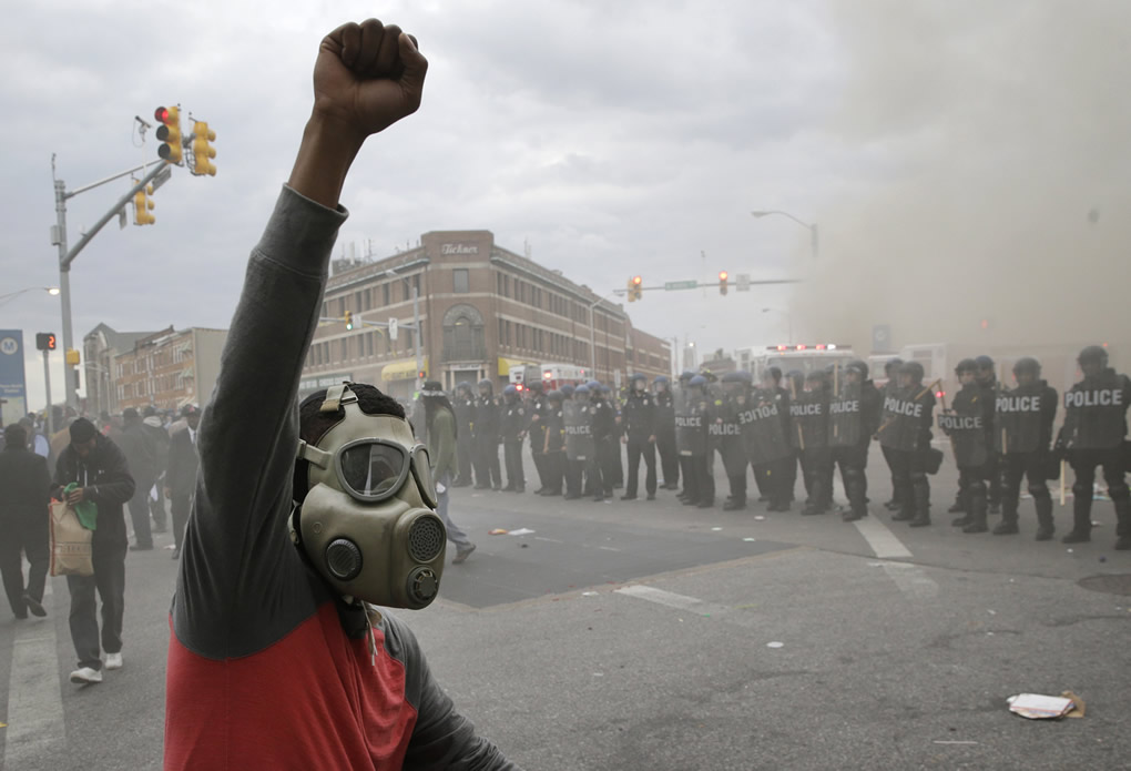 "<div class=""meta image-caption""><div class=""origin-logo origin-image none""><span>none</span></div><span class=""caption-text"">A demonstrator raises his fist as police stand in formation as a store burns, Monday, April 27, 2015, during unrest following the funeral of Freddie Gray in Baltimore. (AP Photo/Patrick Semansky)</span></div>"