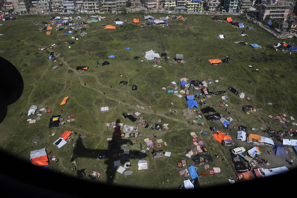 """<div class=""""meta image-caption""""><div class=""""origin-logo origin-image none""""><span>none</span></div><span class=""""caption-text"""">The shadow of an Indian Air Force aircraft carrying relief material is cast on an area where tents are setup by residents in Kathmandu, Nepal, April 27, 2015. (AP Photo/Altaf Qadri)</span></div>"""