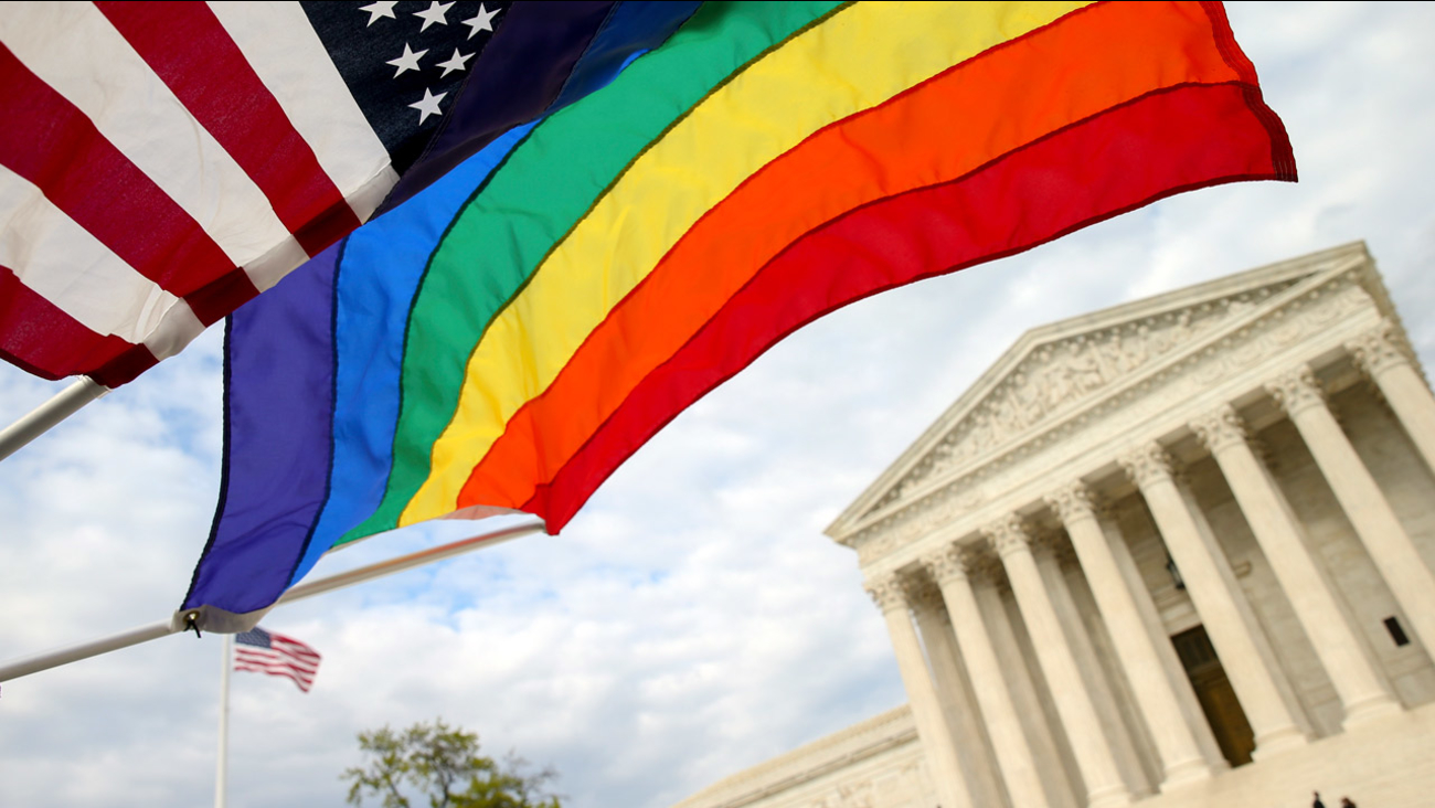 An American flag and a rainbow colored flag flies in front of the Supreme Court in Washington, Monday, April 27, 2015.