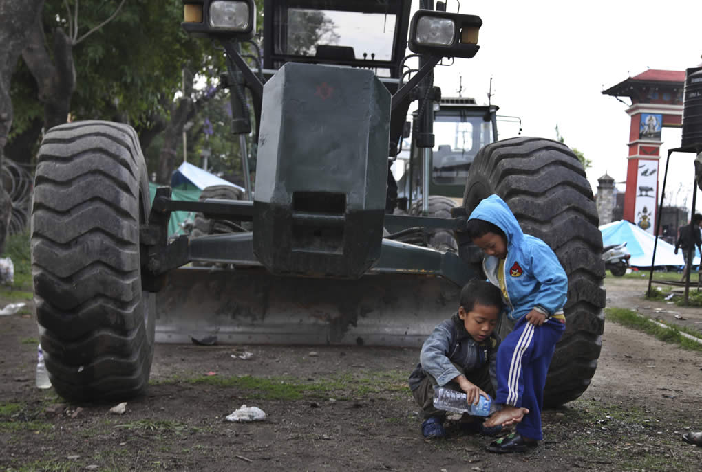 """<div class=""""meta image-caption""""><div class=""""origin-logo origin-image none""""><span>none</span></div><span class=""""caption-text"""">A young Nepalese boy washes the feet of his sibling next to an earth mover at a makeshift camp for the earthquake affected in Kathmandu, Nepal, Tuesday, April 28, 2015. (AP Photo/Altaf Qadri)</span></div>"""