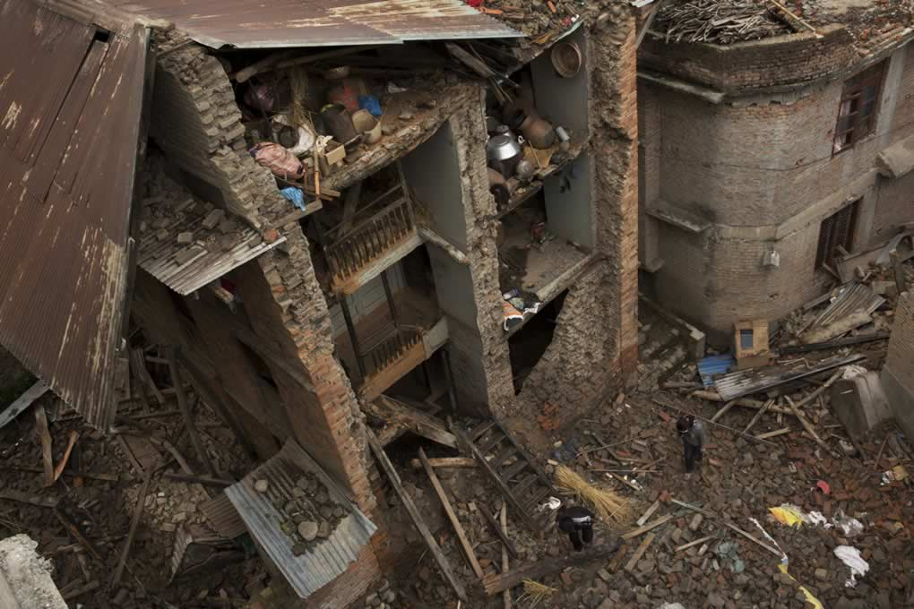 """<div class=""""meta image-caption""""><div class=""""origin-logo origin-image none""""><span>none</span></div><span class=""""caption-text"""">People walk past a house with one side of its walls completely destroyed by the earthquake in Sakhu, on the outskirts of Kathmandu, Nepal, Wednesday, April 29, 2015. (AP Photo/Bernat Amangue)</span></div>"""