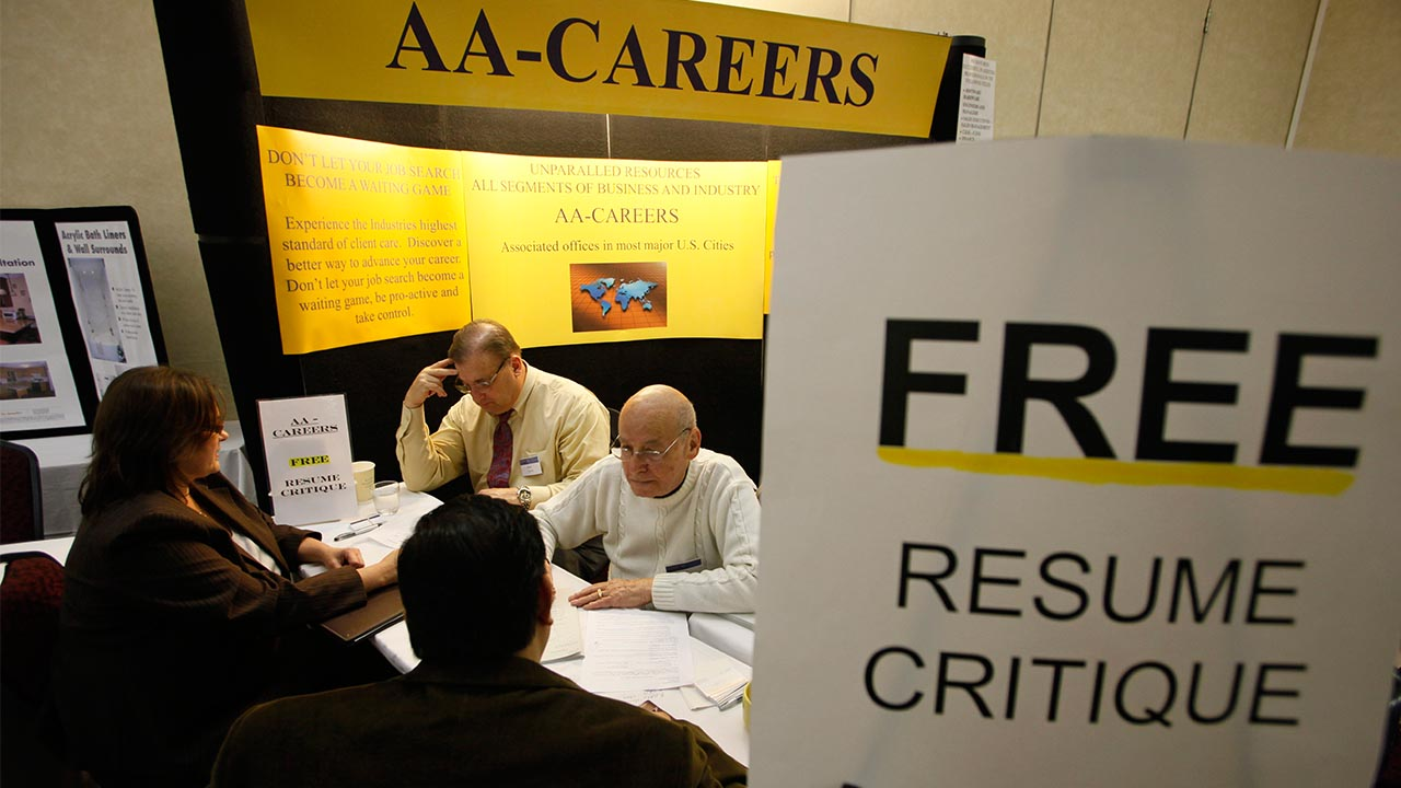In this photo taken Tuesday, March 30, 2010, Paul Davis, top left, and Edwin Pollock, top right, help job seekers with their resumes at a career fair put on by National CareerFairs in San Jose, Calif.