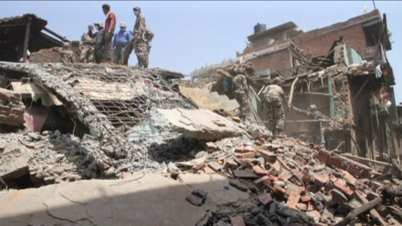 people in Ghorka standing on rubble