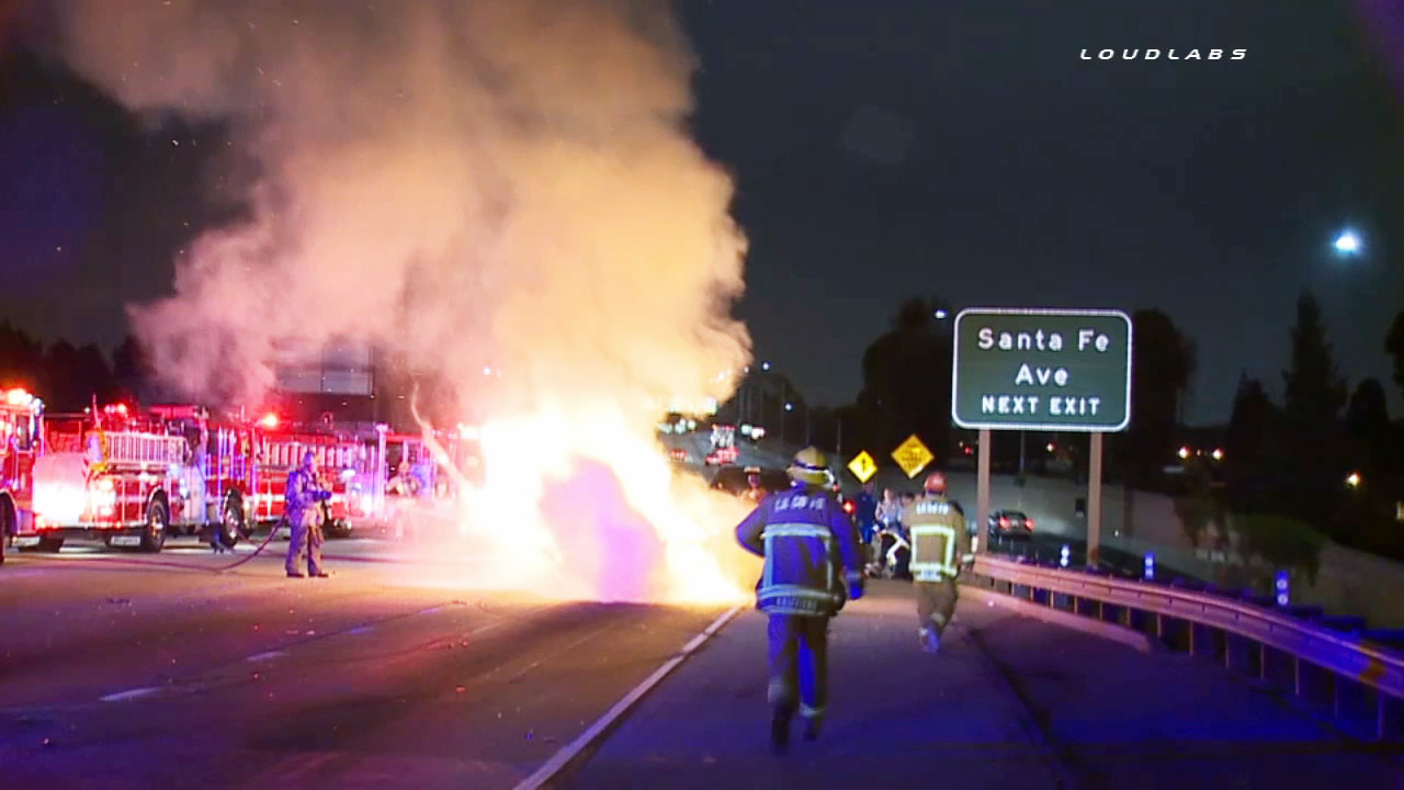 Firefighters douse a car engulfed in flames on the southbound 405 Freeway in Carson on Tuesday, May 5, 2015.