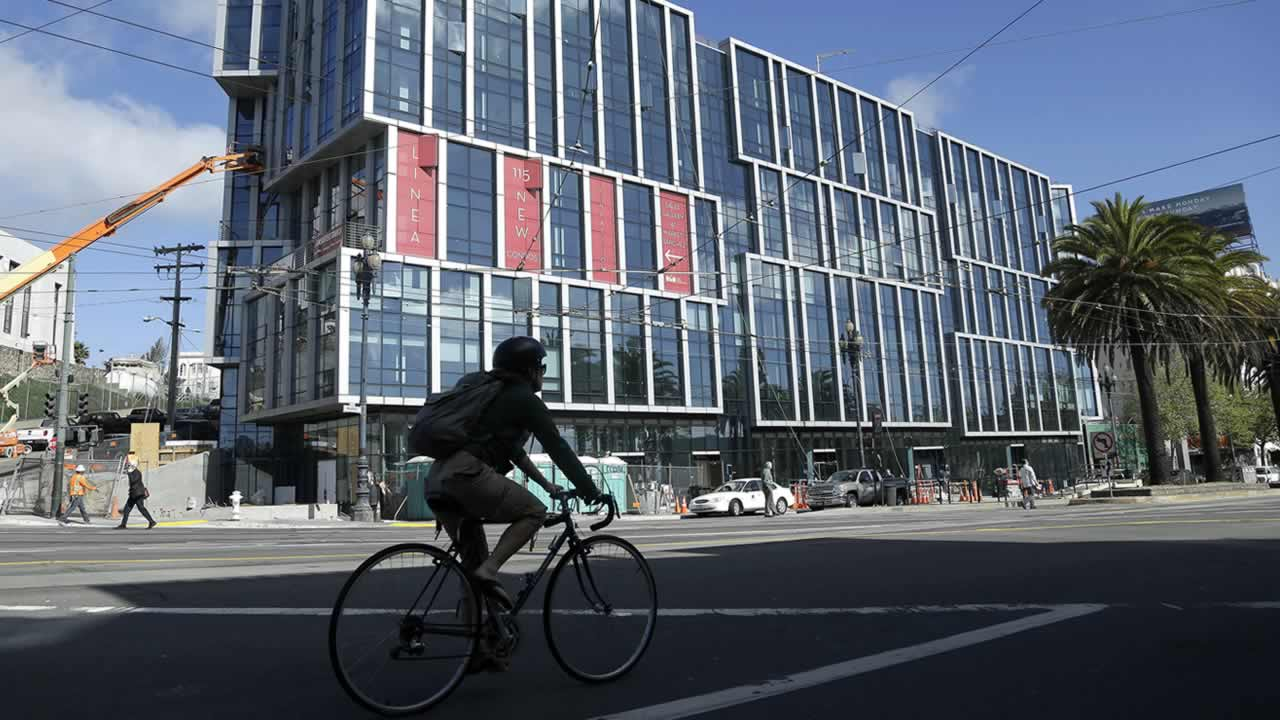 A bicyclist rides in front of the Linea condominium building in San Francisco, Monday, March 17, 2014. (AP Photo/Jeff Chiu)