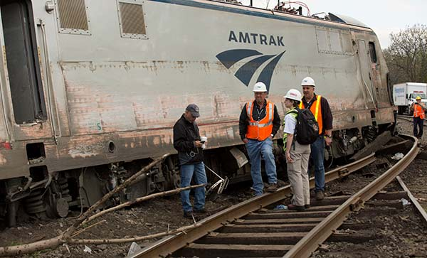 "<div class=""meta image-caption""><div class=""origin-logo origin-image none""><span>none</span></div><span class=""caption-text"">NTSB Recorder Specialist Cassandra Johnson works with officials on the scene of the Amtrak Train #188 Derailment in Philadelphia, PA (National Transportation Safety Board)</span></div>"