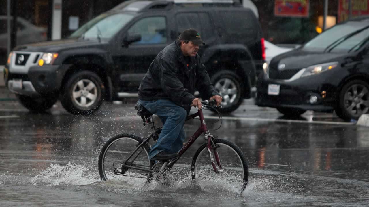 A man rides his bicycle through the flooded intersection of Airport Blvd. and Grand Ave. in South San Francisco, on Thursday, Dec. 11, 2014.