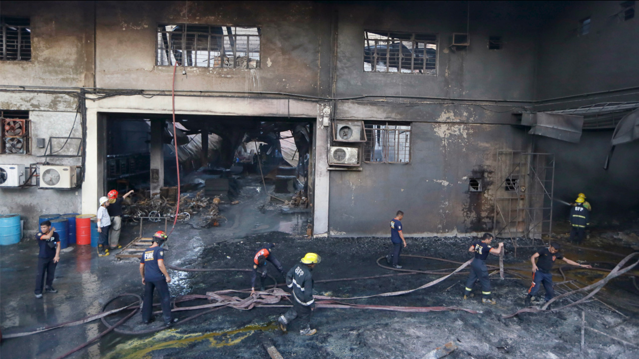 Firemen work to put the fire under control at a still-smoldering Kentex rubber slipper factory in Valenzuela city, a northern suburb of Manila, Philippines, Wednesday, May 13, 2015.