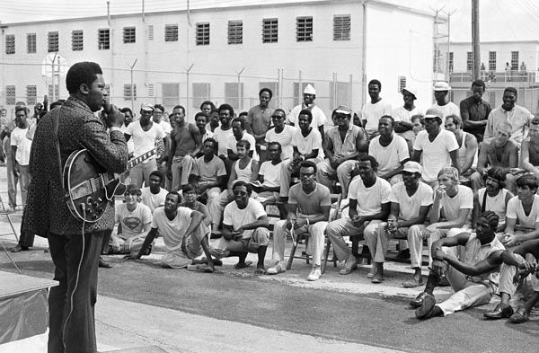 """<div class=""""meta image-caption""""><div class=""""origin-logo origin-image none""""><span>none</span></div><span class=""""caption-text"""">A group of prisoners at the Dade County stockade listen to B.B. King (left) as entertained them outside their cells, Sept. 23, 1971 in Miami, Fla. (AP Photo)</span></div>"""
