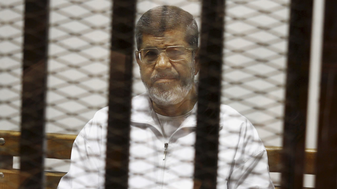 In this May 8, 2014 file photo, Egypt's ousted Islamist President Mohammed Morsi sits in a defendant cage in the Police Academy courthouse in Cairo, Egypt.