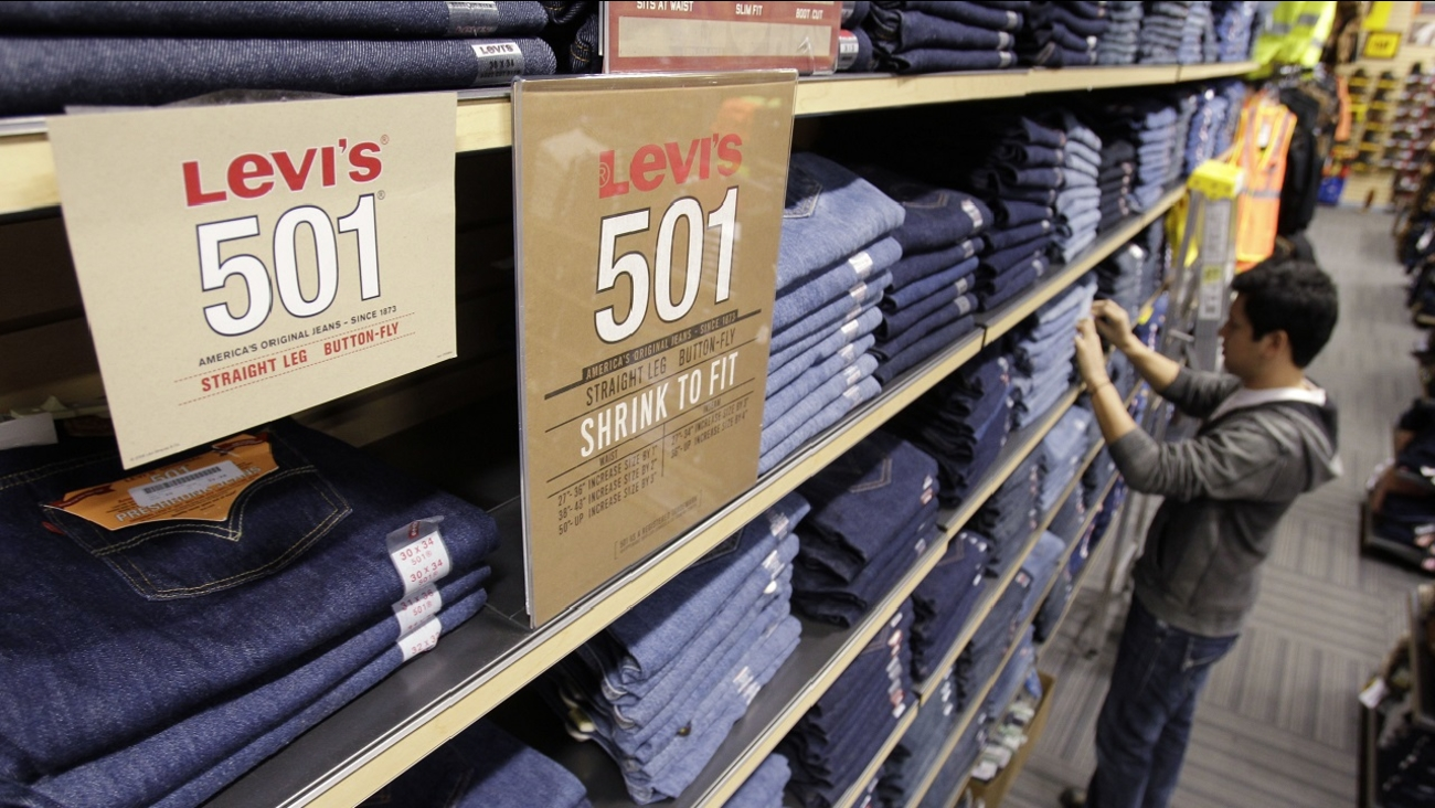 In this Feb. 4, 2011 photo, salesman Jesus Ibarra straightens out Levis jeans on display at a store in Hayward, Calif.