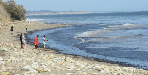 """<div class=""""meta image-caption""""><div class=""""origin-logo origin-image none""""><span>none</span></div><span class=""""caption-text"""">In this photo provided by the Santa Barbara County Fire Department people walk on a beach with an oil slick from a broken pipeline off the central California coast (AP Photo/ Mike Eliason)</span></div>"""