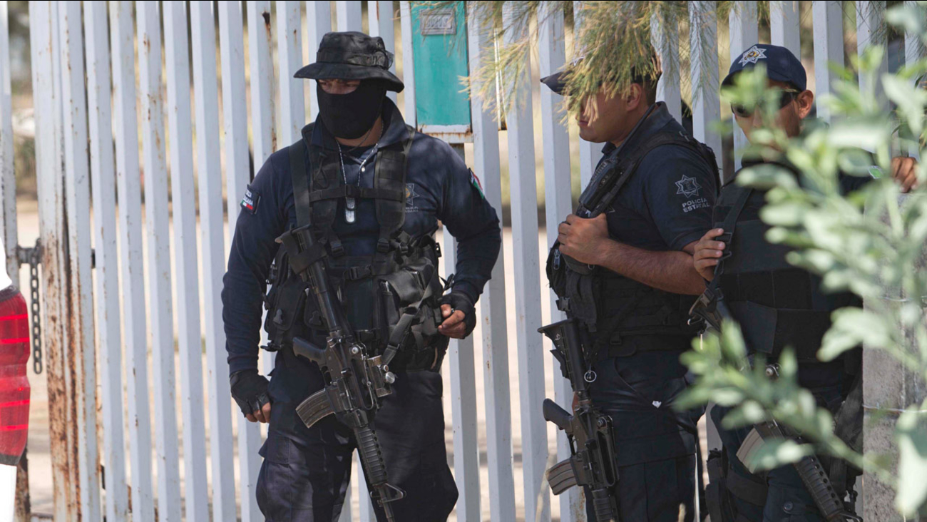Mexican state police stand guard near the entrance of Rancho del Sol, near Vista Hermosa, Mexico, Friday, May 22, 2015.