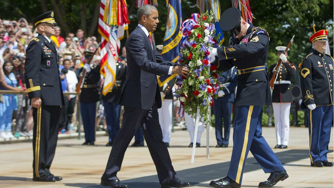 President Barack Obama, accompanied by Maj. Gen. Jeffrey S. Buchanan, left, and Sgt. 1st Class John C. Wirth, lays a wreath at the Tomb of the Unknowns, on Memorial Day, May 25, 2015, at Arlington National Cemetery in Arlington, Va.
