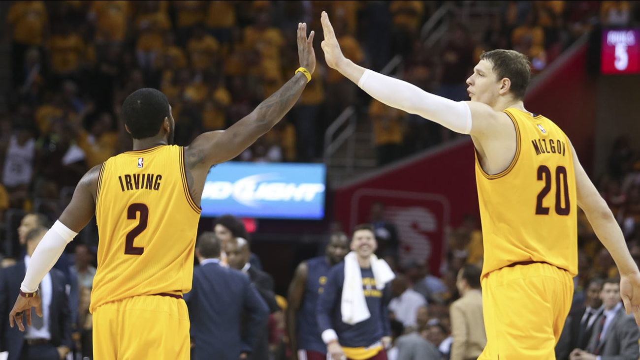 Cleveland Cavaliers' Timofey Mozgov and Kyrie Irving high five each other