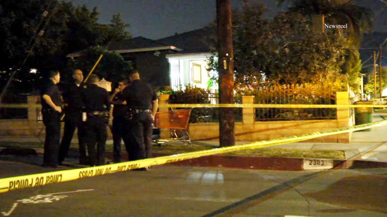 Law enforcement officials stand behind yellow crime scene tape in Eagle Rock, where a man attacked his co-worker with a machete on Tuesday, May 26, 2015.