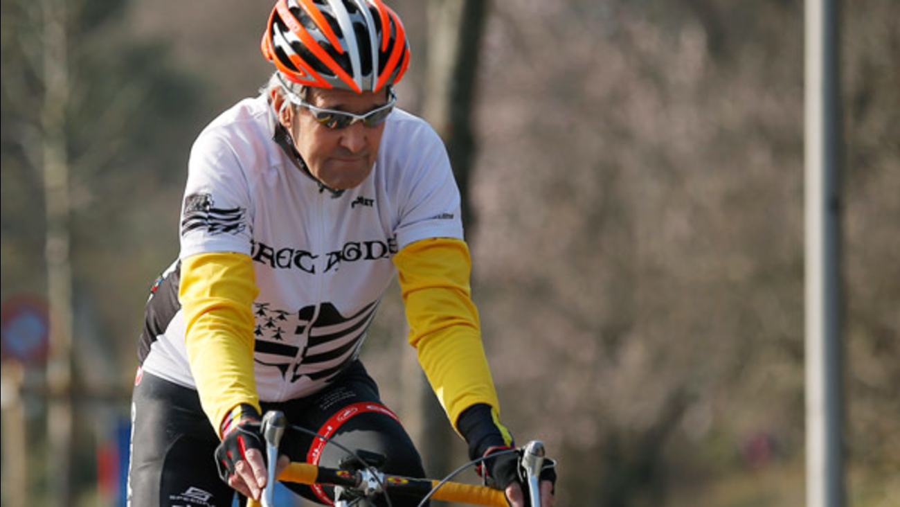 U.S Secretary of State John Kerry rides his bicycle along the shore of Lake Geneva in Lausanne, Switzerland, Wednesday March 18, 2015.
