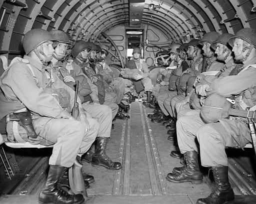 "<div class=""meta image-caption""><div class=""origin-logo origin-image none""><span>none</span></div><span class=""caption-text"">American paratroopers, heavily armed, sit inside a military plane as they soar over the English Channel en route to the Normandy French coast. (AP Photo/ XNBG)</span></div>"