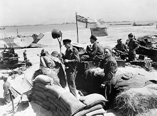 "<div class=""meta image-caption""><div class=""origin-logo origin-image none""><span>none</span></div><span class=""caption-text"">British troops make their way through low water and up the beach after leaving landing craft which transported them across the Channel to the Normandy beachhead. (AP Photo/ XNBG)</span></div>"