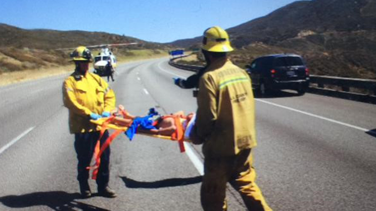Los Angeles County firefighters transport a patient injured after a car falls 100 feet off the 5 Freeway near Castaic on Sunday, June 7, 2015.