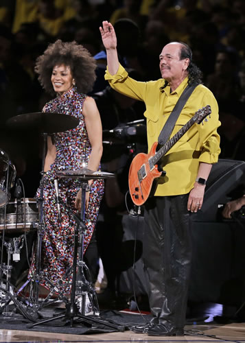 """<div class=""""meta image-caption""""><div class=""""origin-logo origin-image none""""><span>none</span></div><span class=""""caption-text"""">Carlos Santana, right, waves after he and his wife Cindy Blackman Santana performed the national anthem before Game 2 of basketball's NBA Finals. (AP Photo/Ben Margot)</span></div>"""