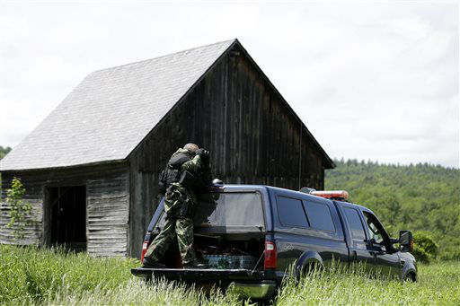 """<div class=""""meta image-caption""""><div class=""""origin-logo origin-image none""""><span>none</span></div><span class=""""caption-text"""">A heavily armed law enforcement officer looks over a field through binoculars during a search for two escaped killers near Boquet, N.Y., Tuesday, June 9, 2015. (AP Photo/ Seth Wenig)</span></div>"""
