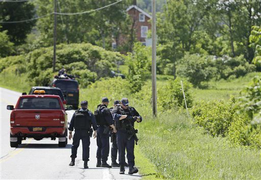 """<div class=""""meta image-caption""""><div class=""""origin-logo origin-image none""""><span>none</span></div><span class=""""caption-text"""">Heavily armed law enforcement agents patrol the edge of road during a search for two escaped killers near Boquet, N.Y., Tuesday, June 9, 2015. (AP Photo/ Seth Wenig)</span></div>"""