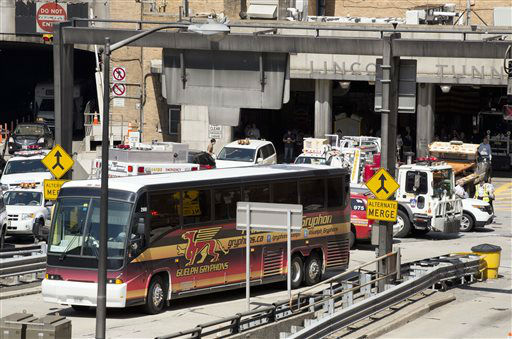 """<div class=""""meta image-caption""""><div class=""""origin-logo origin-image none""""><span>none</span></div><span class=""""caption-text"""">A private bus that had been carrying Canadian school children drives out of the Lincoln Tunnel following the accident. (AP Photo/ Mark Lennihan)</span></div>"""