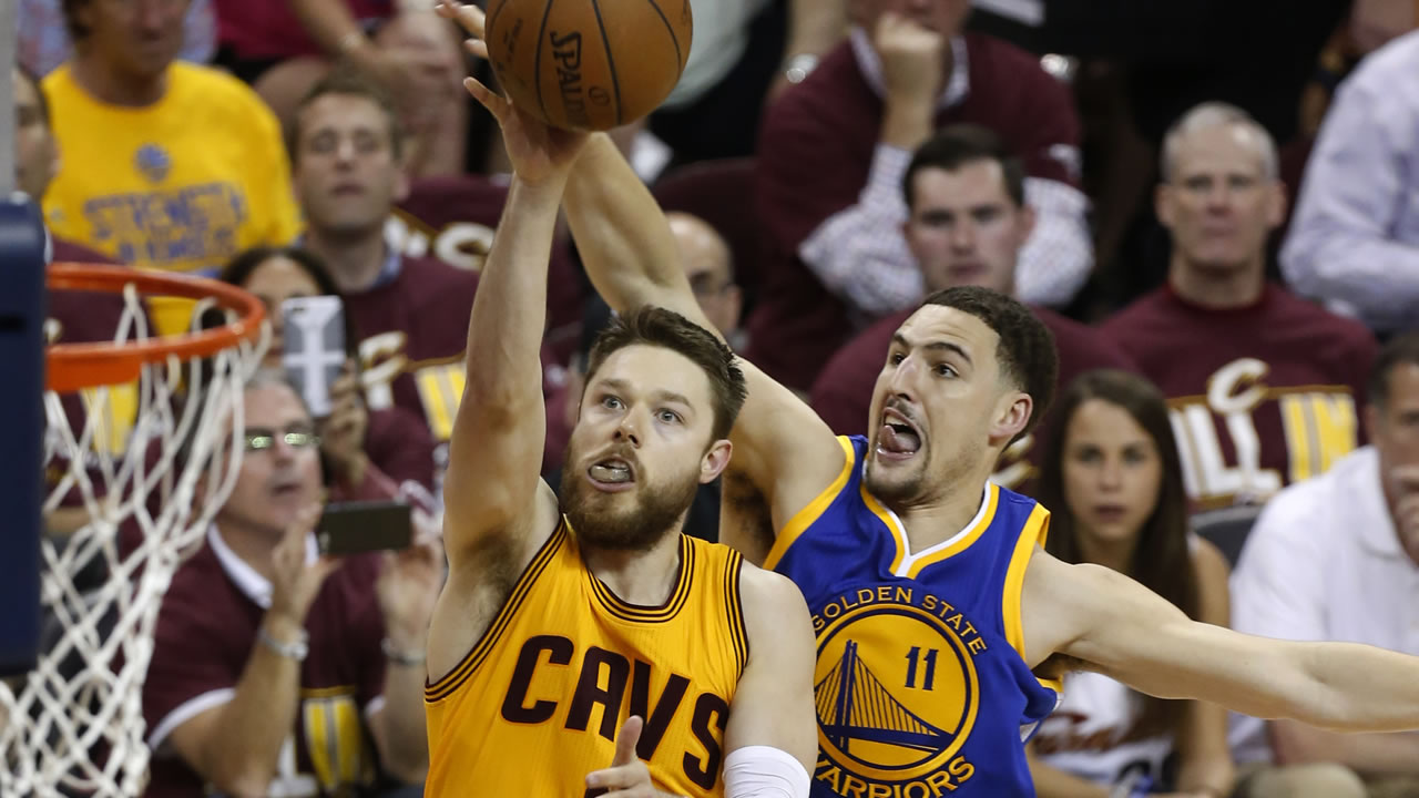 Cavaliers guard Matthew Dellavedova shoots in front of Warriors guard Klay Thompson during Game 3 of the NBA Finals in Cleveland, Tuesday, June 9, 2015.