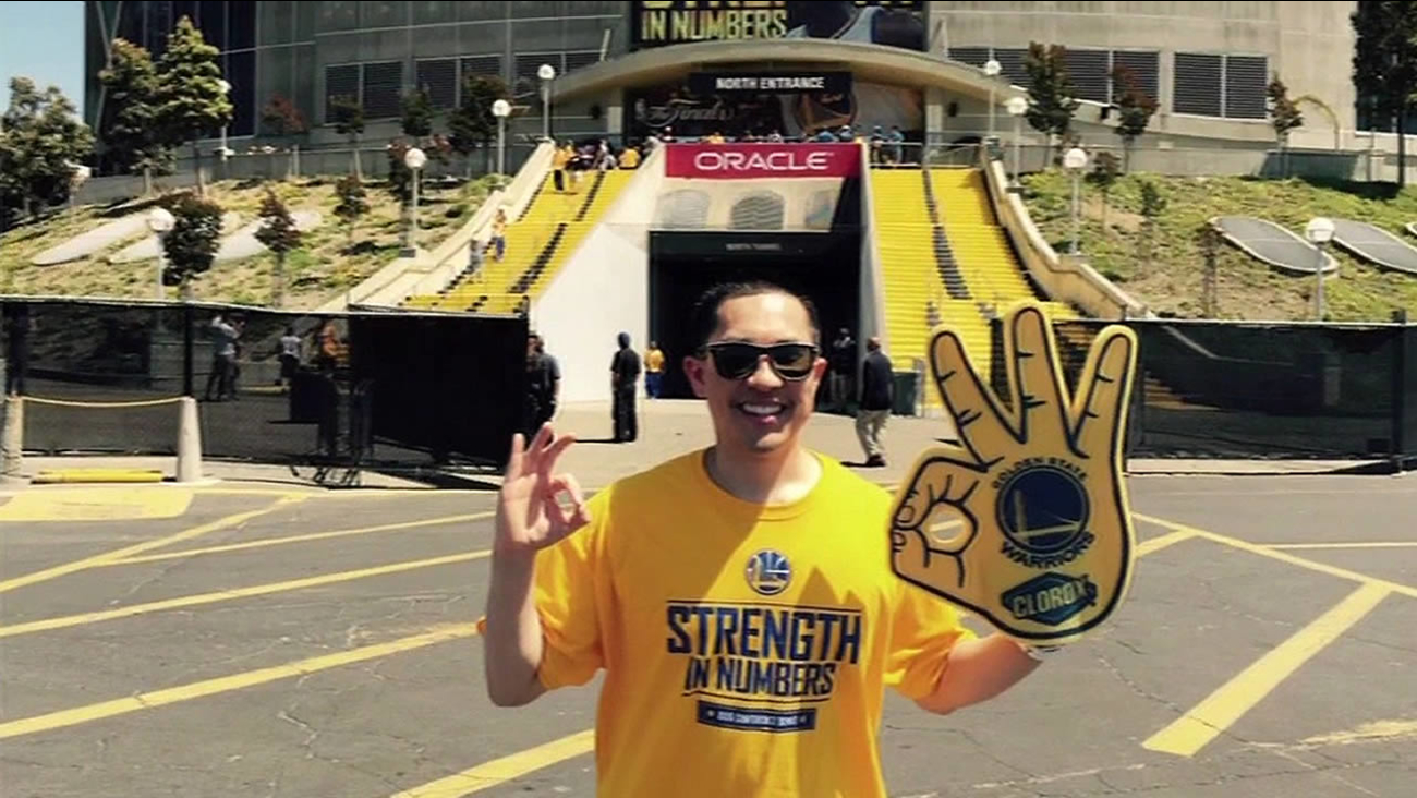 Warriors fan Henry Yu poses in front of Oracle Arena
