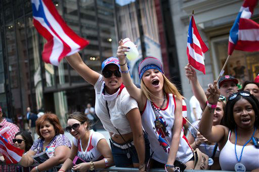 <div class='meta'><div class='origin-logo' data-origin='none'></div><span class='caption-text' data-credit='AP Photo/ Kevin Hagen'>Arsenia Fuentes, center left, and Sarah Dones, center right, cheer for a passing float as the Puerto Rican Day Parade makes its way up New York's Fifth Ave. (AP Photo/Kevin Hagen)</span></div>