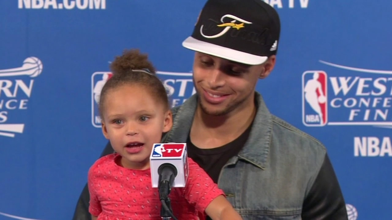 File photo - Warriors' Stephen Curry speaks at a press conference while he hold his daughter.