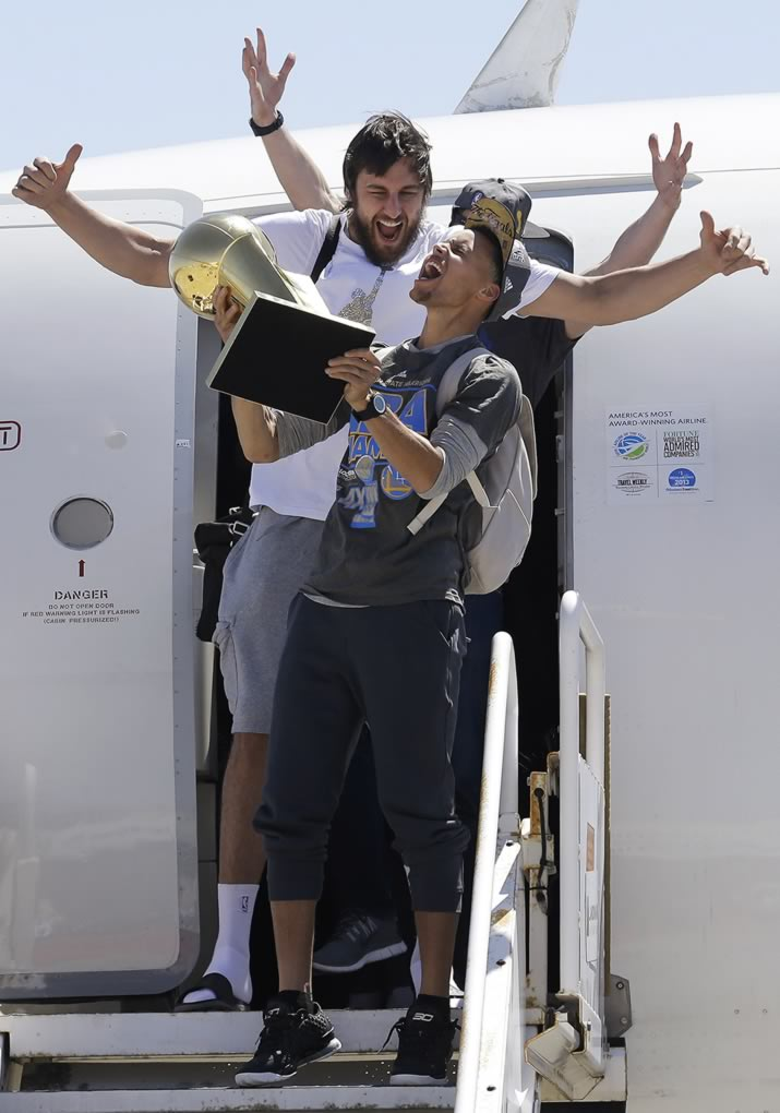 "<div class=""meta image-caption""><div class=""origin-logo origin-image none""><span>none</span></div><span class=""caption-text"">Warriors guard Stephen Curry yells as he carries the NBA championship trophy in front of center Andrew Bogut after the team's flight landed in Oakland, Calif., June 17, 2015. (AP Photo/Jeff Chiu)</span></div>"
