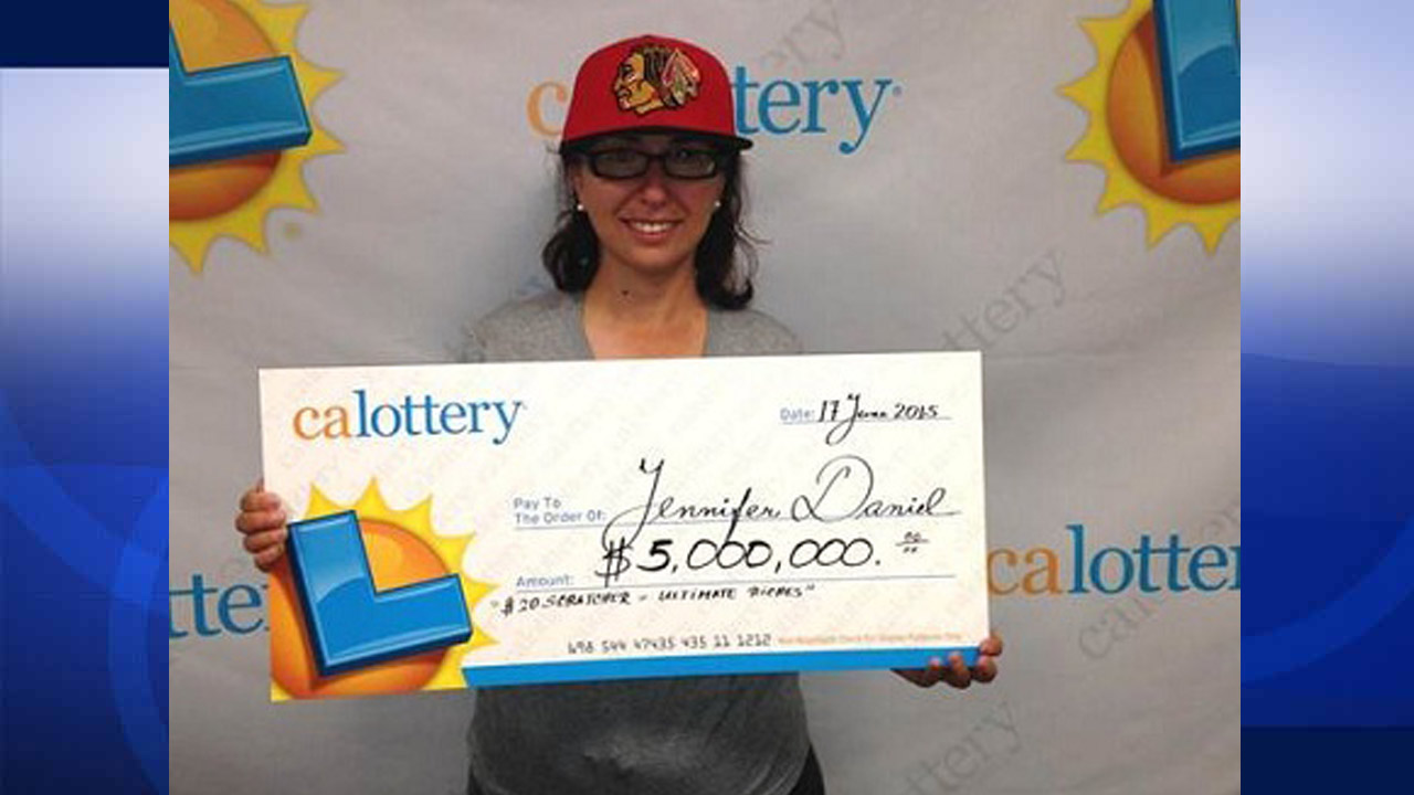 Jennifer Daniel holds up her $5 million check she won on a scratcher ticket in Modesto, California.