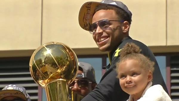 Golden State Warriors' Steph Curry and daughter Riley ride a float during the team's victory parade on Friday, June 19, 2015 in Oakland, Calif.
