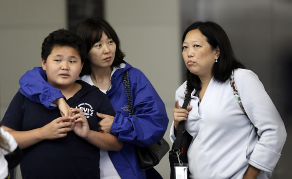 <div class='meta'><div class='origin-logo' data-origin='none'></div><span class='caption-text' data-credit=''>Onlookers talk outside of The Reflection Room where friends and relatives of Asiana Flight 214 passengers await news following the plane crash. Saturday,July 6, 2013. (AP Photo/Marcio Jose Sanchez)</span></div>