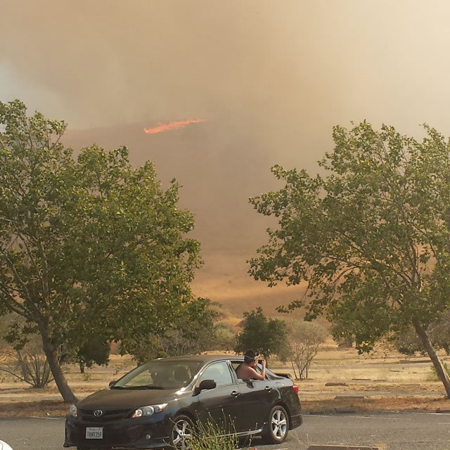 """<div class=""""meta image-caption""""><div class=""""origin-logo origin-image none""""><span>none</span></div><span class=""""caption-text"""">A man snaps a photo as a brush fire burns in Contra Loma Regional Park in Antioch, Calif. on Wednesday, June 24, 2015. (Photo submitted by shorty007s/Instagram)</span></div>"""