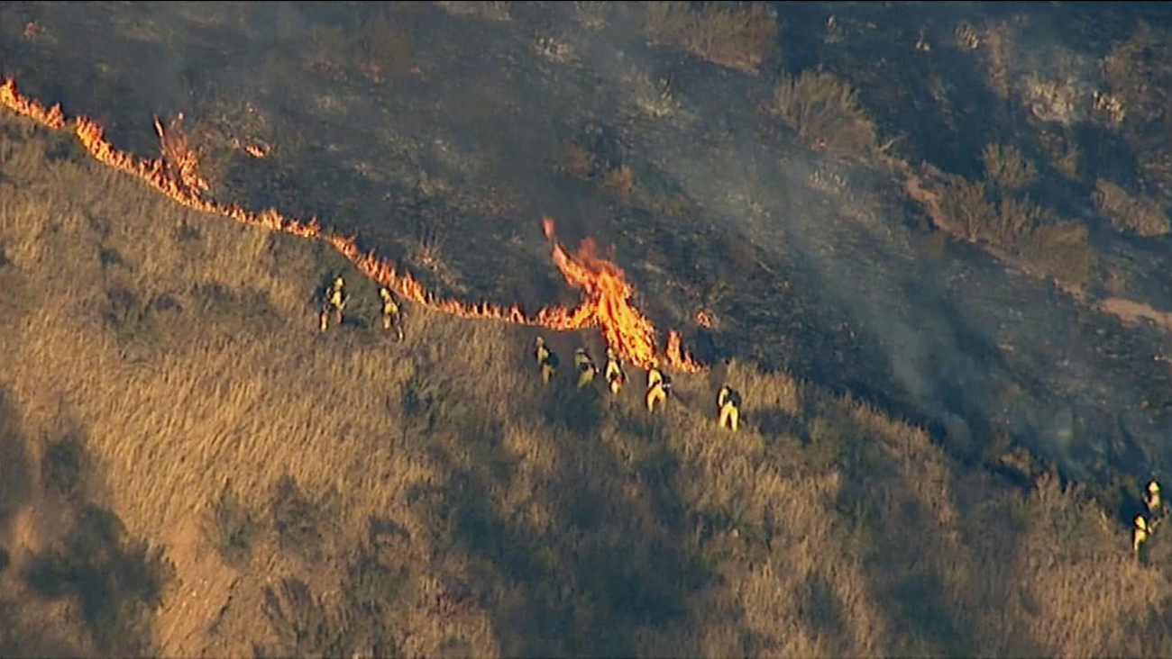 Firefighters walk beside a brush fire and attempt to put out the flames on Thursday, June 25, 2015 in the San Bernardino foothills.