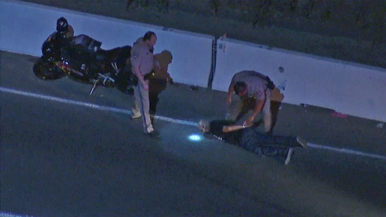 California Highway Patrol officers handcuff a motorcyclist who led them on a high-speed chase through multiple freeways on Thursday, June 25, 2015.