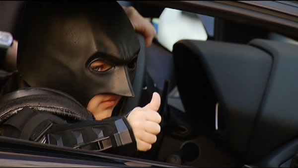Batkid gives the crowd a thumbs-up.