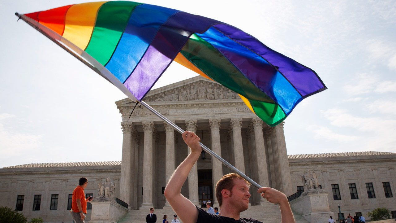 John Becker, 30, of Silver Spring, Md., waves a rainbow flag in support of gay marriage outside of the Supreme Court in Washington, Thursday June 25, 2015.