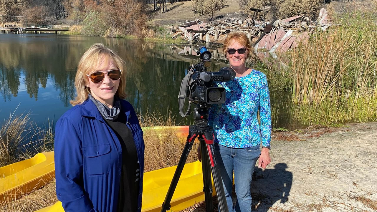 ABC7's Cheryl Jennings and photographer Cathy Cavey stand next to the water at what's left of Camp Okizu.