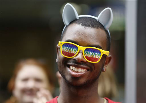"<div class=""meta image-caption""><div class=""origin-logo origin-image none""><span>none</span></div><span class=""caption-text"">Julian Sims, of Meriden, Conn., wears ""Hello Sunny"" glasses and rainbow-colored earrings as he watches floats and people parade down New York's Fifth Avenue. (AP Photo/ Kathy Willens)</span></div>"
