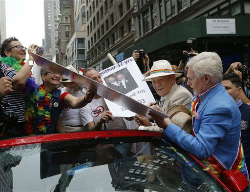 "<div class=""meta image-caption""><div class=""origin-logo origin-image none""><span>none</span></div><span class=""caption-text"">Actors Sir Ian McKellan, second from right, watches as Sir Derek Jacobi autographs a poster for two legally married women. (AP Photo/ Kathy Willens)</span></div>"