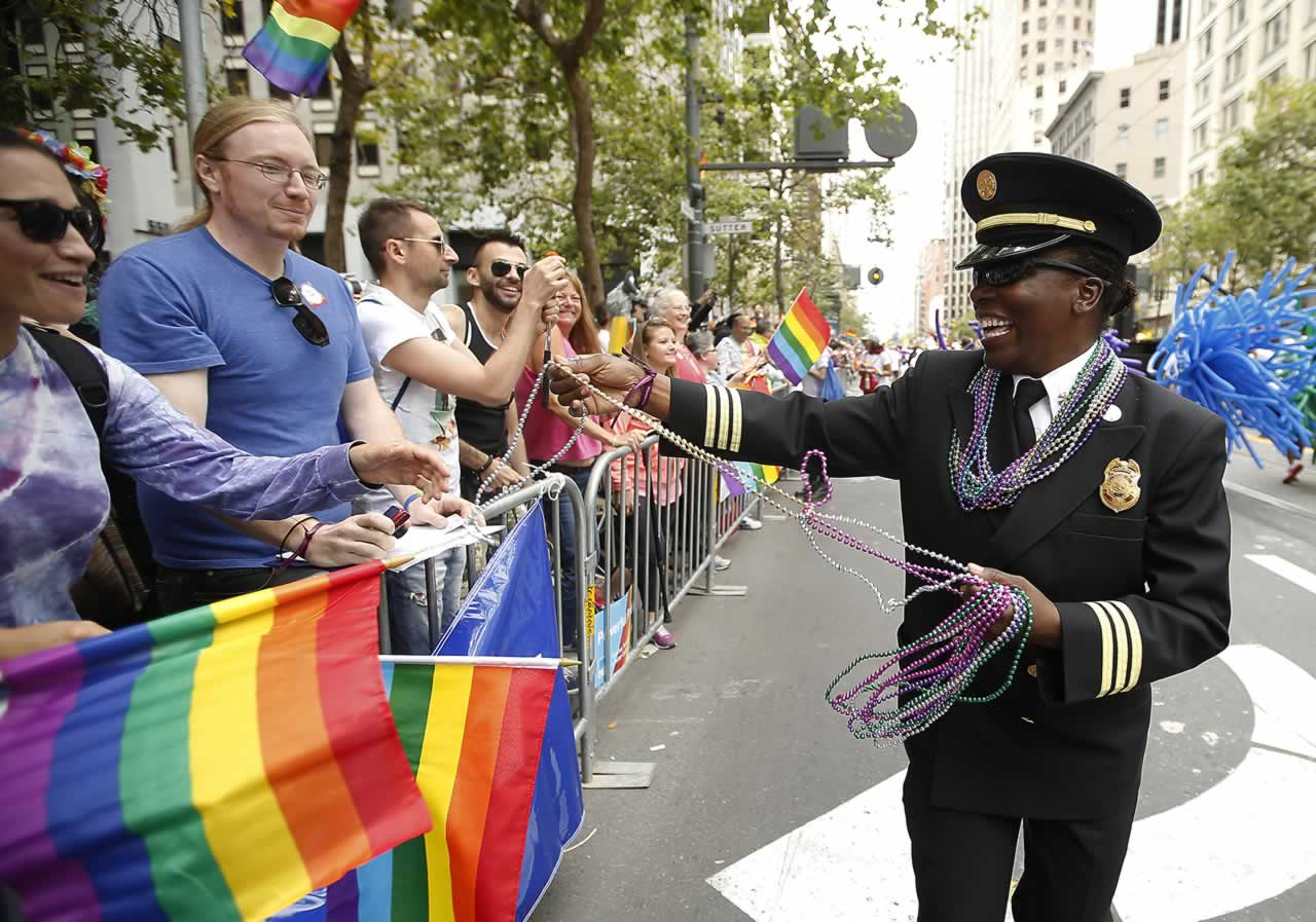 "<div class=""meta image-caption""><div class=""origin-logo origin-image none""><span>none</span></div><span class=""caption-text"">SFFD's Deputy Chief Raemona Williams, right, passes out beaded necklaces to the crowd during the 45th annual San Francisco Gay Pride parade Sunday, June 28, 2015, in San Francisco. (AP Photo/ Tony Avelar)</span></div>"