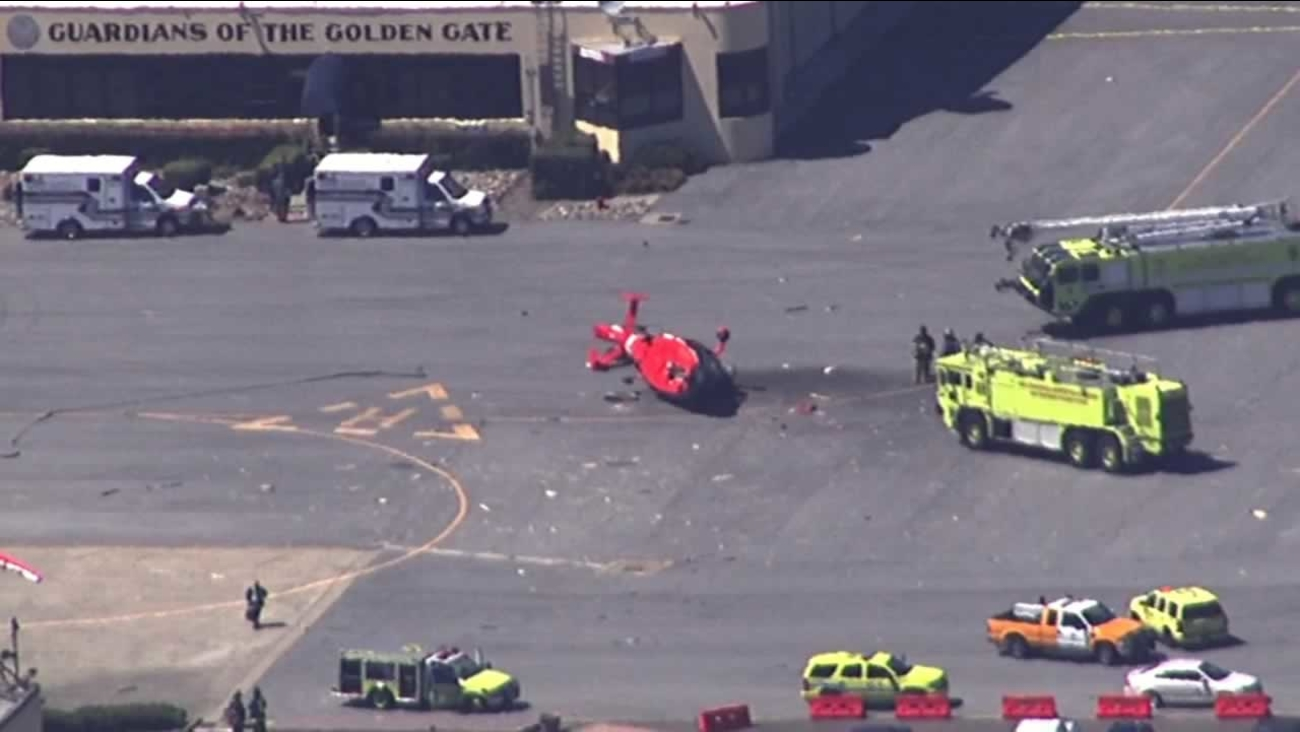 A Coast Guard helicopter landed on it is side after it crashed on an airfield at the San Francisco International Airport, Monday, June 29, 2015.