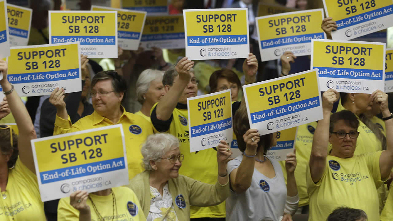 Right-to-die legislation supporters hold up signs of support during a hearing on the bill in the Senate Health Committee at the Capitol in Sacramento, Calif., March 25, 2015. (AP Photo/Rich Pedroncelli)
