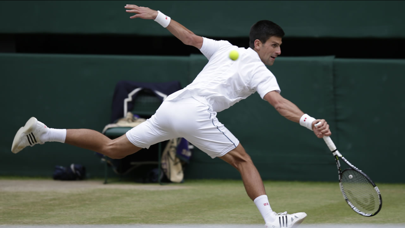 Novak Djokovic returns a ball to Roger Federer during the men's singles final at the All England Lawn Tennis Championships in Wimbledon, London, Sunday July 12, 2015.
