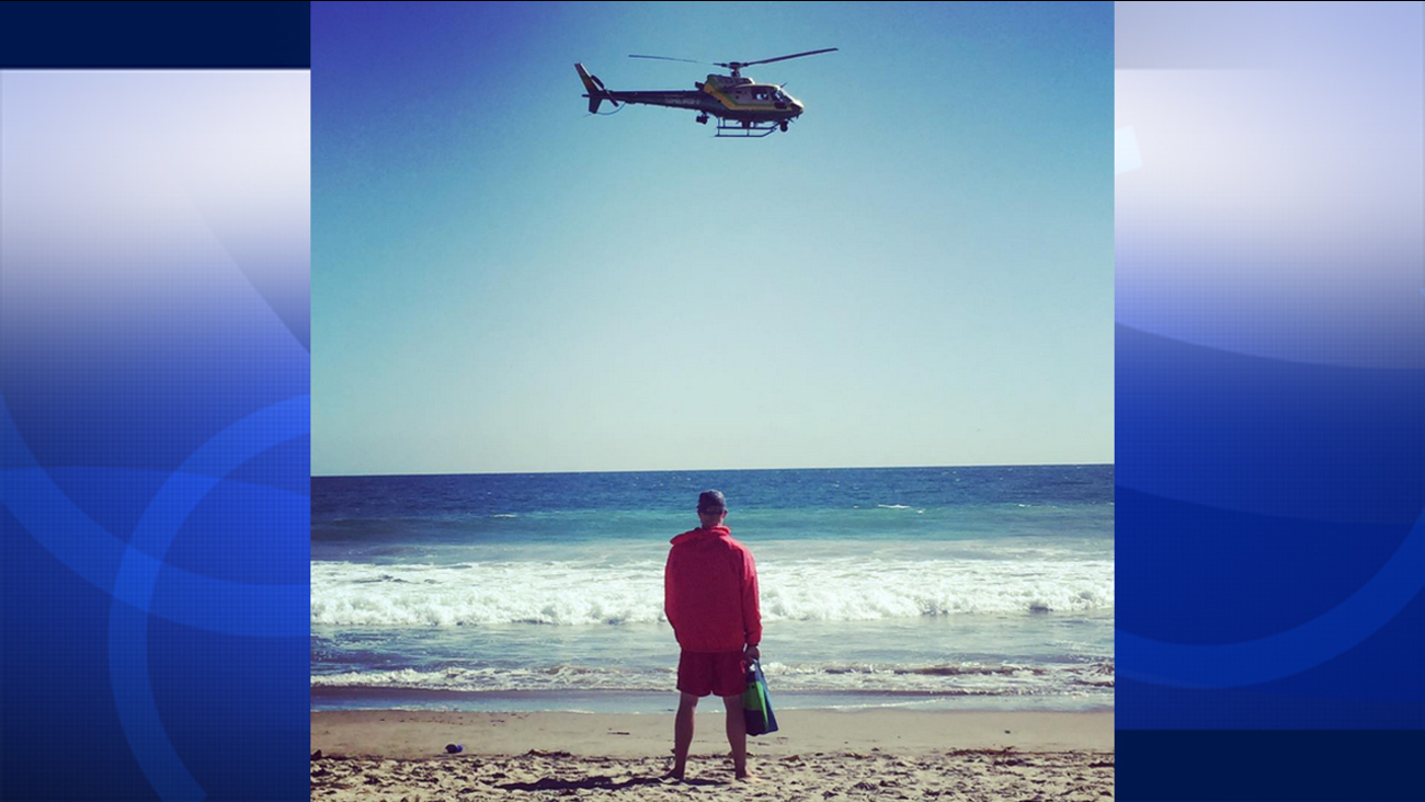 A Los Angeles County Sheriff's Department helicopter flies in search of a missing swimmer in Zuma Beach on Sunday, July 12, 2015.